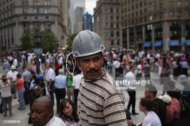 People gather outside of their buildings in lower Manhattan after being evacuated following an earthquake on August 23 2011 in New York City The...
