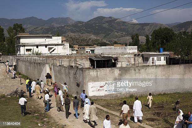 People gather outside Osama Bin Laden's compound, where he was killed during a raid by U.S. Special forces, May 3, 2011 in Abottabad, Pakistan. Bin...