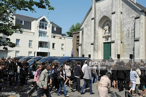 People gather outside the church of Saint Felix in the French western city of Nantes to attend a funeral ceremony on April 28 2011 in the memory of...