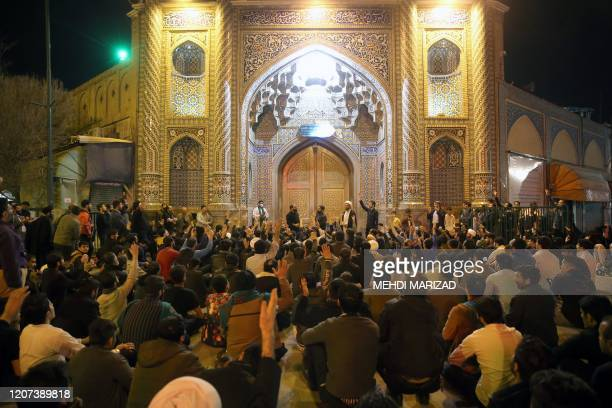 People gather outside the closed doors of the Fatima Masumeh shrine in Iran's holy city of Qom on March 16 2020 Iran closed four key Shiite...