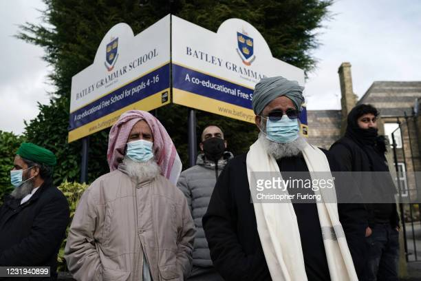 People gather outside the gates of Batley Grammar School, after a teacher was suspended for showing an image of the Prophet Muhammad in class, on...