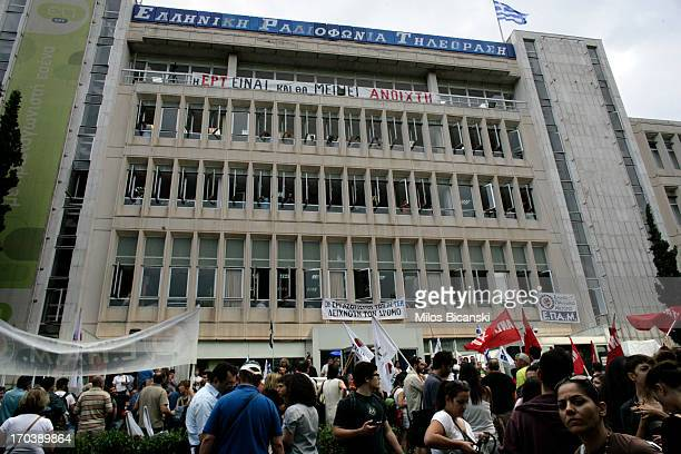 People gather outside the headquarters of the Greek public broadcaster ERT in support of staff following the announcement of corporations closure on...
