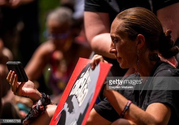 People gather outside the Hennepin County Government Center and watch a live stream of the sentencing hearing for Derek Chauvin on June 25, 2021 in...