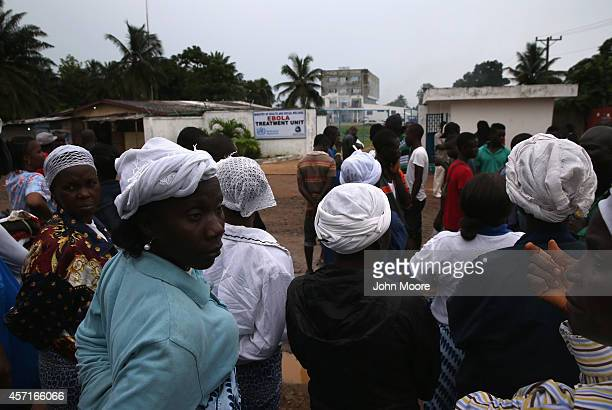 People gather outside the Island Clinic Ebola treatment center on October 13 2014 in Monrovia Liberia A planned strike was averted as most nurses and...