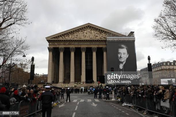 People gather outside the La Madeleine Church after the funeral ceremony in tribute to late French singer Johnny Hallyday on December 9 2017 in Paris...