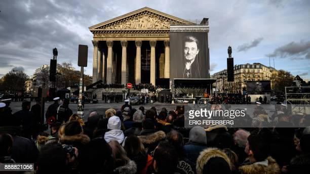 People gather outside the La Madeleine Church at the end of the funeral ceremony in tribute to late French singer Johnny Hallyday on December 9 2017...