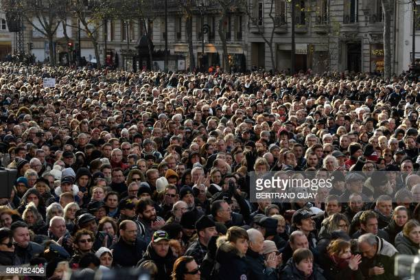 People gather outside the La Madeleine Church during the funeral ceremony in tribute to late French singer Johnny Hallyday on December 9 2017 in...