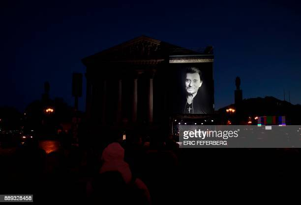 People gather outside the La Madeleine Church early morning before the funeral ceremony in tribute to late French singer Johnny Hallyday on December...