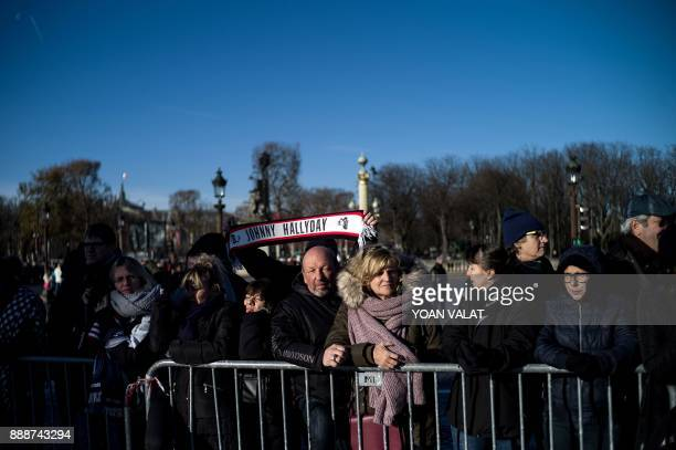 People gather outside the La Madeleine Church prior to the funeral ceremony during a 'popular homage' in tribute to late French singer Johnny...