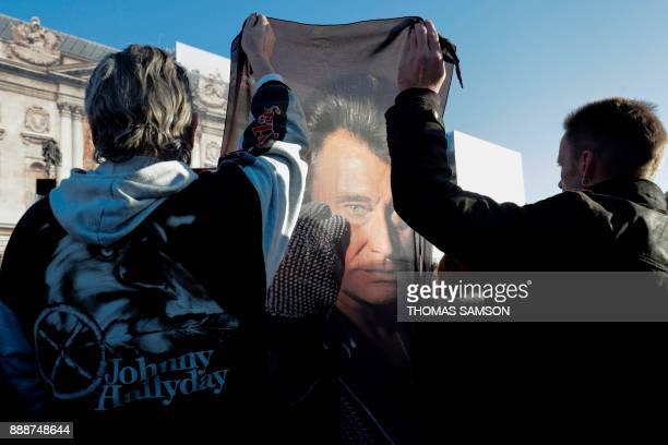 People gather outside the La Madeleine Church prior to the funeral ceremony in tribute to late French singer Johnny Hallyday on December 9 2017 in...