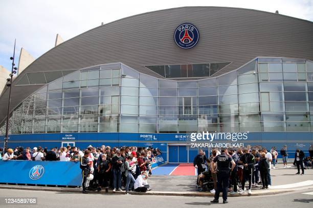 People gather outside the Parc des Princes stadium in Paris as Argentinian football player Lionel Messi is expected to arrive on August 9 a day after...