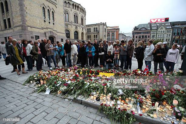 People gather outside the Parliament in Oslo city center to lay down flowers and candles after a memorial vigil following Friday's twin extremist...