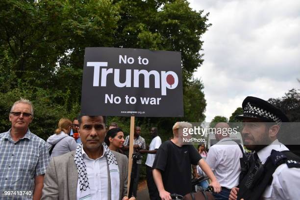 People gather outside the security fencing around Winfield House the London residence of US ambassador Woody Johnson to protest against President...