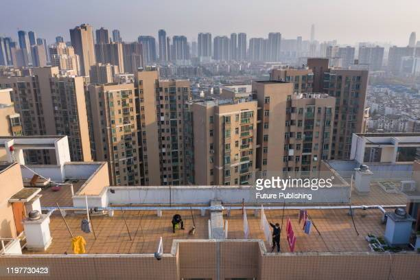 People gather quilts on the roof of a building in Wuhan, Hubei Province, China, January 30, 2020. - PHOTOGRAPH BY Costfoto / Barcroft Media