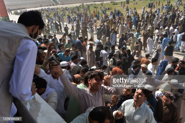 People gather to apply for Pakistan visas at a football stadium following a stampede that killed at least 11 women, in Jalalabad on October 21, 2020....