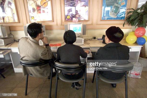 People gather to browse the Internet at a Cyber cafe in Beijing 24 January. After months of procrastination and under pressure from users, China has...