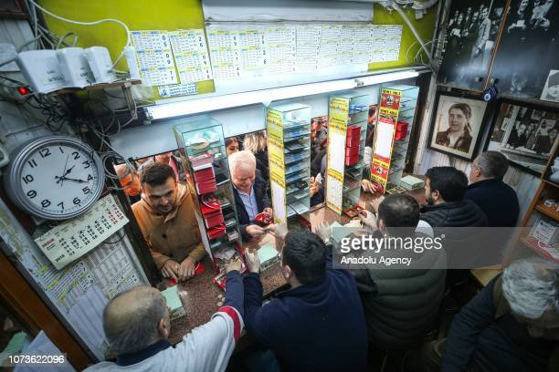 People gather to buy lottery tickets at Nimet Abla kiosk the most famous ticket agency in Istanbul for Turkey's New Year lottery draw in Eminonu...