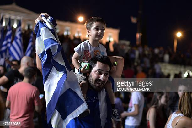 People gather to celebrate in Athens on July 5 2015 after the first exitpolls of the Greek referendum Over 60 percent of Greeks rejected further...