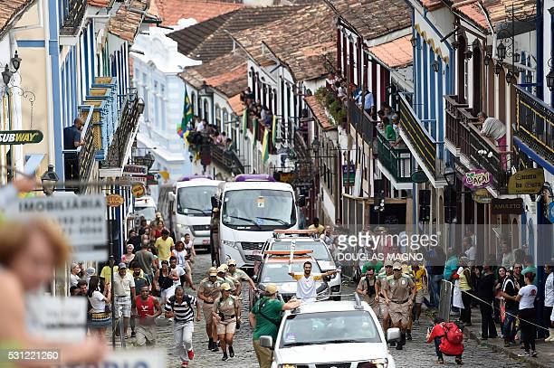 TOPSHOT People gather to celebrate the arrival of the Olympic torch in Ouro Preto Minas Gerais Brazil on May 13 2016 / AFP / DOUGLAS MAGNO