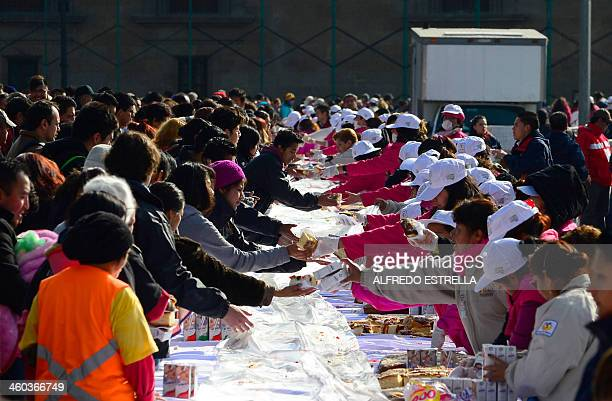 People gather to get a piece of the traditional Rosca de Reyes in Mexico City on January 3 2014 The Rosca de Reyes was distributed among 200000...