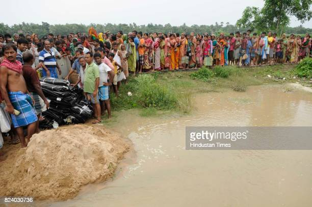 People gather to get relief material like polythene sheet in flood affected Chiknan village of Howrah on July 28 2017 near Kolkata India Flood...