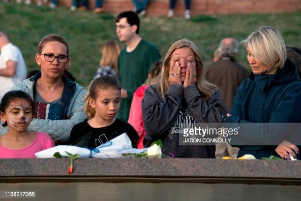 People gather to honor and remember loved ones at the Columbine Memorial at Clement Park in Littleton Colorado during a community vigil for the 20th...