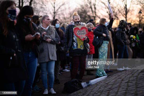 People gather to lay flowers and pay their respects at a vigil on Clapham Common, where floral tributes have been placed for Sarah Everard on March...