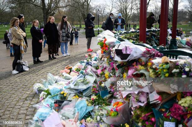 People gather to lay flowers and pay their respects on Clapham Common where floral tributes have been placed for Sarah Everard on March 13, 2021 in...