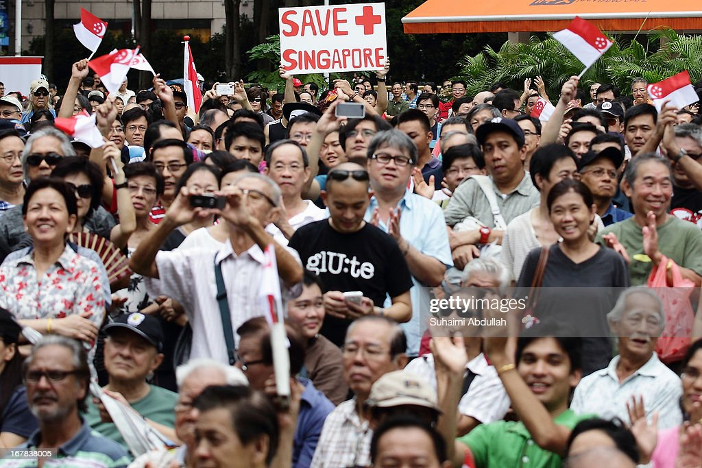 People gather to listen to a speaker during a protest against the government's White Paper on Population and labour-related matters that affect Singaporeans at Speakers' Corner in Hong Lim Park on May 1, 2013 in Singapore. Thousands of protesters gathered today in an inaugural labour day protest against the 6.9 million population government white paper that revealed it could increase 30% to 6.9 million by 2030, angering residents who already see a strain on housing, transportation and healthcare. This is a follow up protest after one was held on 16 Feb, 2013 organised by the same organiser, transitioning.org