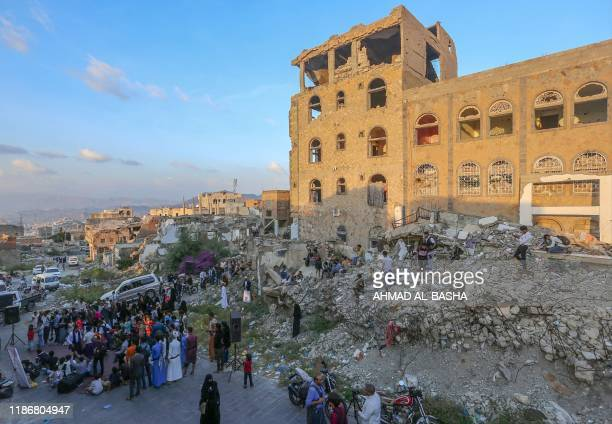 People gather to listen to Yemeni musicians during a street performance amids collapsed buildings in Yemen's third city of Taez, on December 6, 2019....
