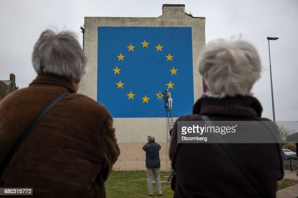People gather to look at a mural depicting a European Union flag being chiseled by a workman on the side of a disused building near the ferry...