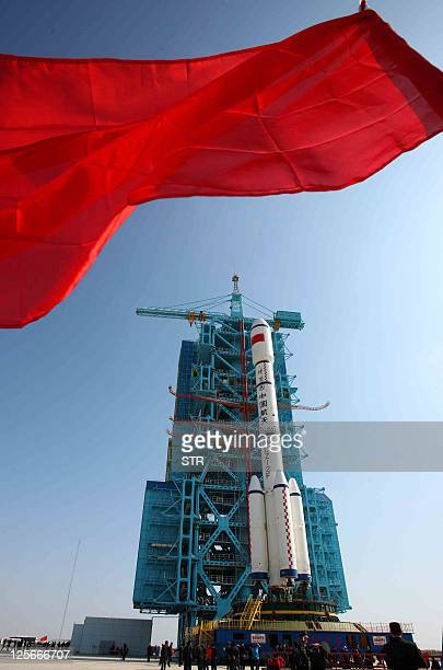 People gather to look at China's Long March 2F rocket which will take the Tiangong1 space module into space as it is rolled out onto a launch...