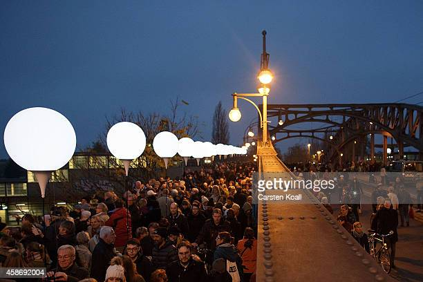 People gather to look the illumination on Boesebruecke bridge in Bornholmer Strasse where 25 years before thousands of East Germans first crossed...