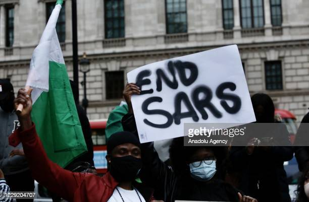 People gather to march to Parliament Square to stage a protest against the attacks towards demonstrators during the ongoing protests in Nigeria...
