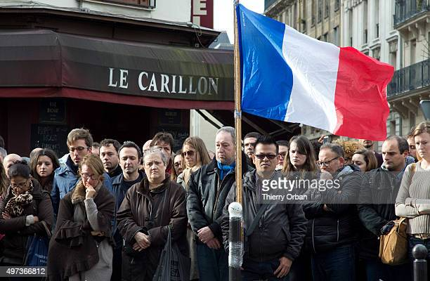 People gather to observe a minute silence outside the Le Carillon restaurant in memory of the victims of the Paris terror attacks last Friday on...