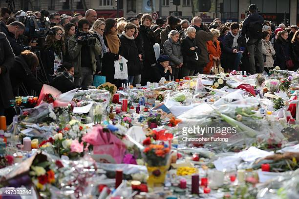 People gather to observe a minutesilence at the Place de la Republique in memory of the victims of the Paris terror attacks last Friday on November...