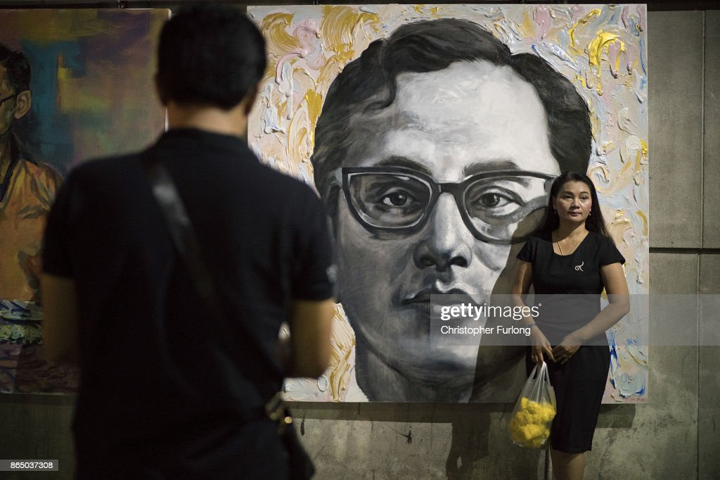 People gather to pay their respects next to a painting of Thailand's late King Bhumibol Adulyadej as the city prepares for his cremation on October 22, 2017 in Bangkok, Thailand. The world's longest serving monarch King Bhumibol Adulyadej died on October 13, 2016. Rehearsals for the five day funeral of the much loved king are taking place around Bangkok's Grand Palace. The ceremonies will take place over five days culminating in the cremation of the king's body in a grand Royal Crematorium on October 26th.