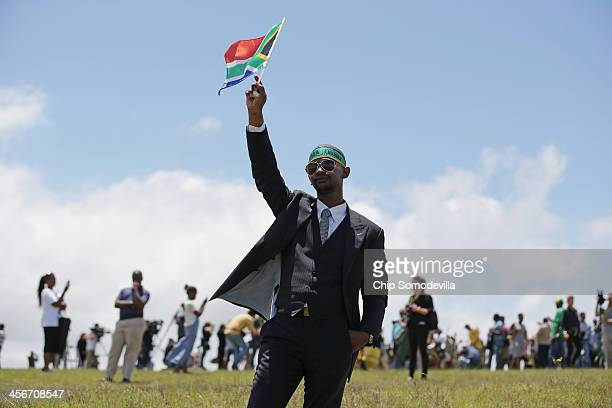 People gather to pay their respects on the hills above former South African President Nelson Mandela's home village during his state funeral December...
