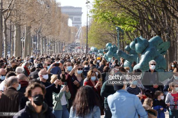 """People gather to peruse sculpture of characters from the comic strip """"Le Chat"""" by Belgian cartoonist Philippe Geluck displayed in an outdoors..."""