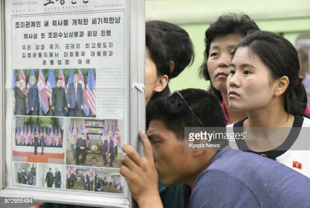 People gather to read the official newspaper of North Korea's ruling Workers' Party at a subway station in Pyongyang on June 13 as it reports the...