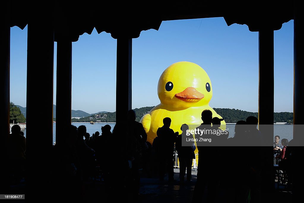 People gather to see a giant Rubber Duck by Dutch conceptual artist Florentijin Hofman at Summer Palace Kunming Lake on September 26, 2013 in Beijing, China. After touring 13 cities in 10 countries, the giant rubber duck will be in at Summer Palace from September 26 to October 26.