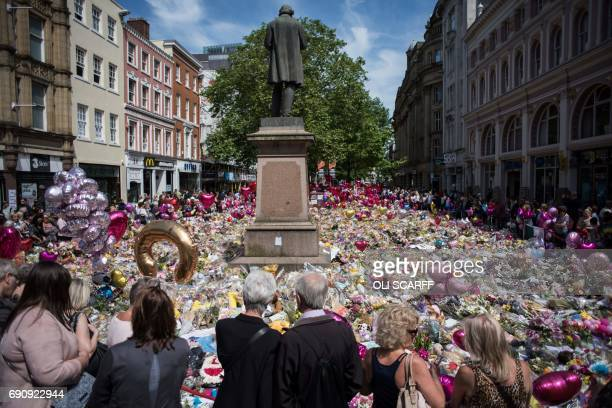 People gather to see flowers and messages of support in St Ann's Square in Manchester northwest England on May 31 placed in tribute to the victims of...