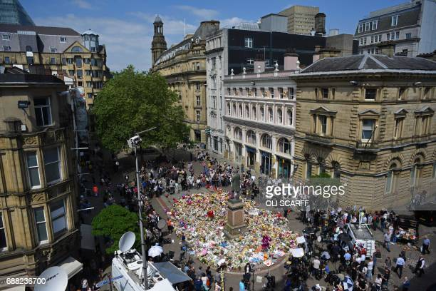 People gather to see flowers and messages of support left around a statue of Richard Cobden in St Ann's Square in Manchester, northwest England on...