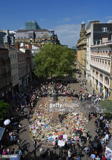 People gather to see flowers and messages of support left around a statue of Richard Cobden in St Ann's Square in Manchester northwest England on May...