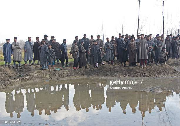 People gather to see the debris of crashed Indian military aircraft in central Kashmir's Budgam on February 27 2019