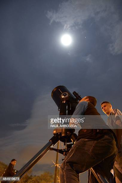 People gather to see the moon head into a total lunar eclipse on April 15 2014 in the municipality of Copacabana near Medellin Antioquia department...