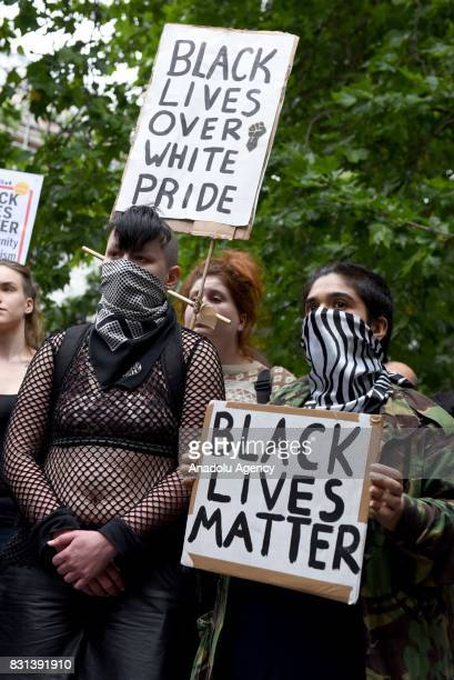 People gather to stage a demonstration as they hold placards during the 'Stand up to Racism' protest outside the US Embassy in London on August 14...