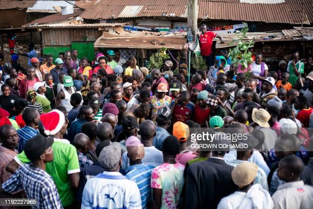 People gather to watch 18yearold Isaac Namolo from Gisu tribe being circumcised on a street at Kibera slum in Nairobi Kenya on January 6 2020