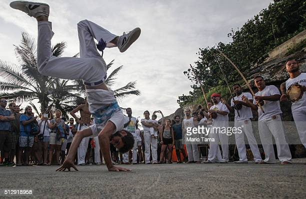 People gather to watch a capoeira performance along Arpoador rock a popular tourist destination in Rio next to Ipanema beach on February 28 2016 in...