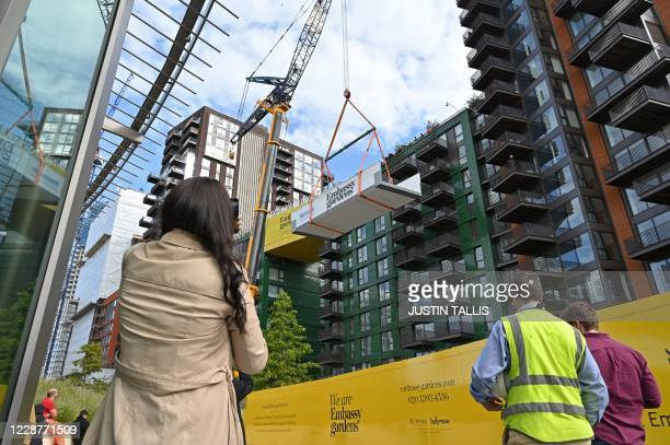 People gather to watch a crane lift an transparent acrylic swimming pool bridge that will be fixed between two apartment blocks at Embassy Gardens...